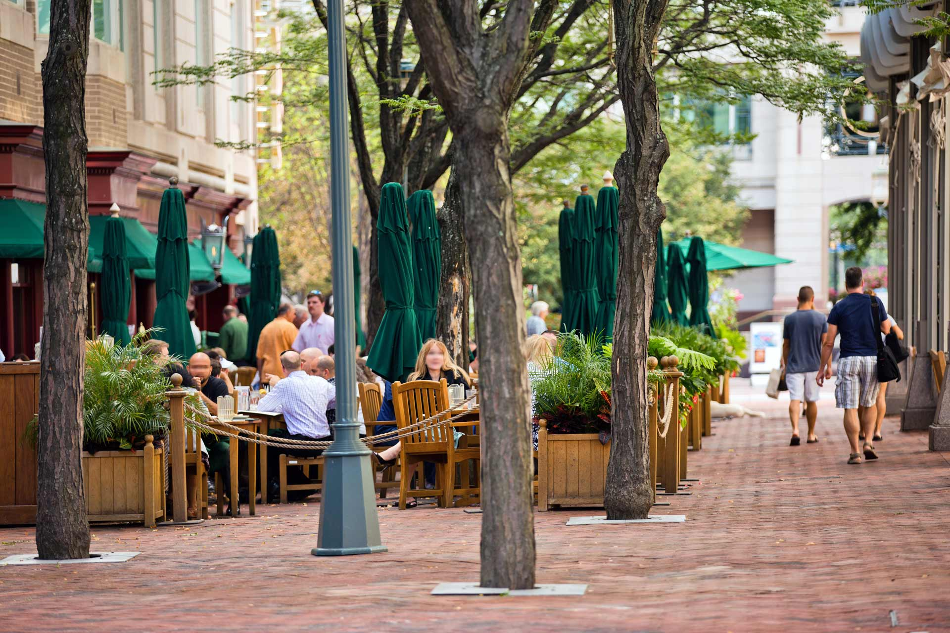 Brick sidewalks and large trees with Clyde's outdoor dining in background