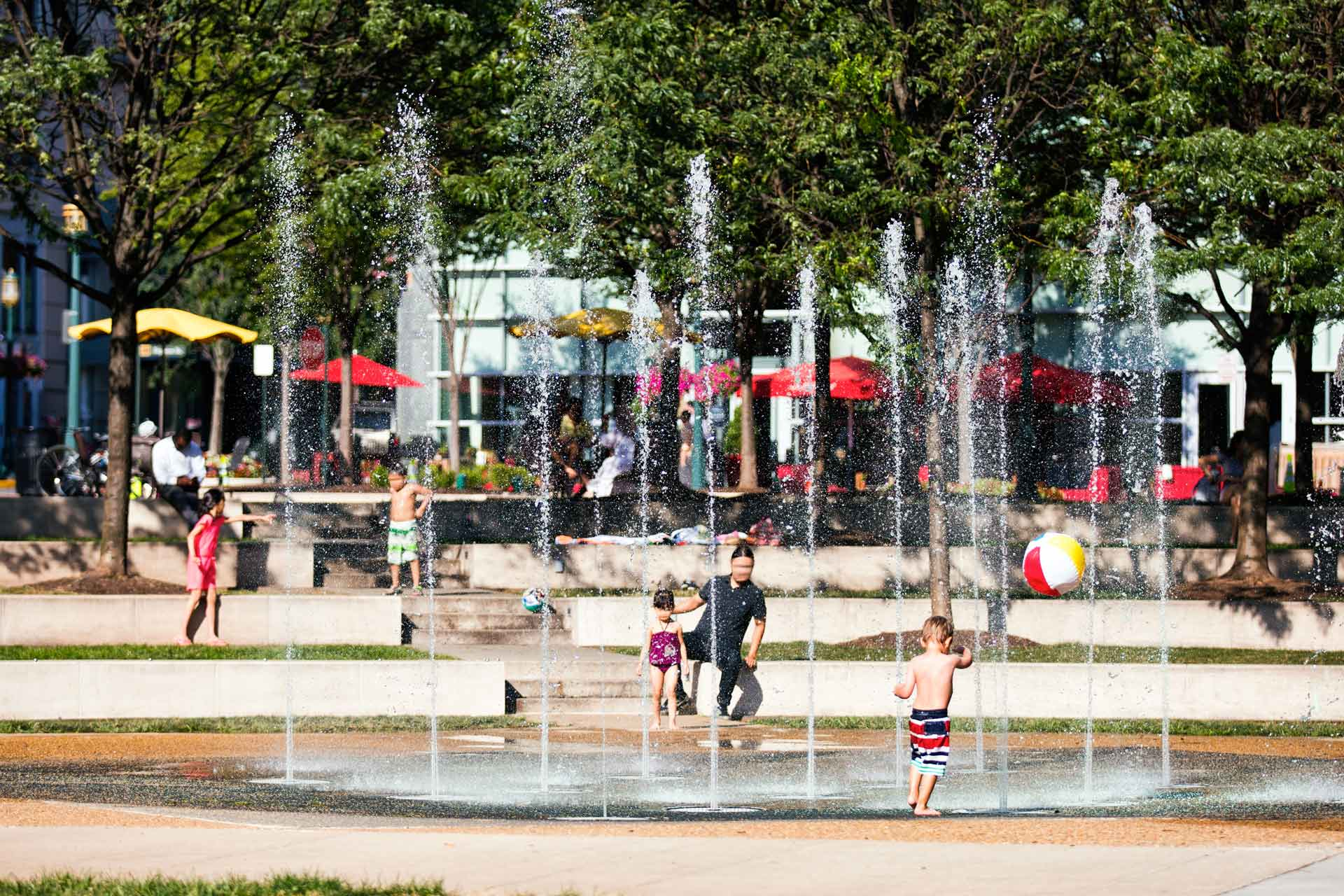 Children playing in the splash fountain on a warm, sunny day