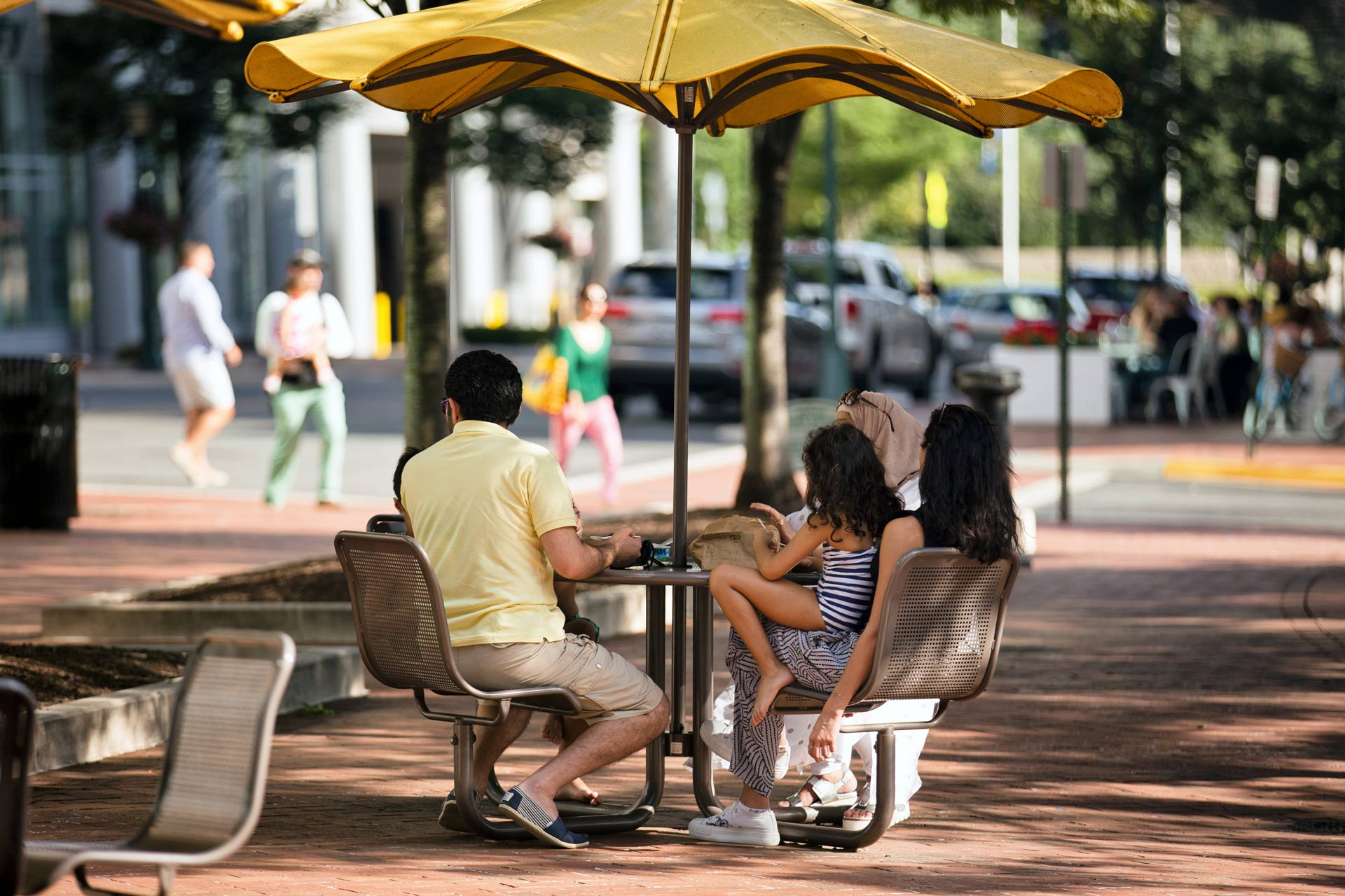Family seated at a shaded table in Reston Town Center