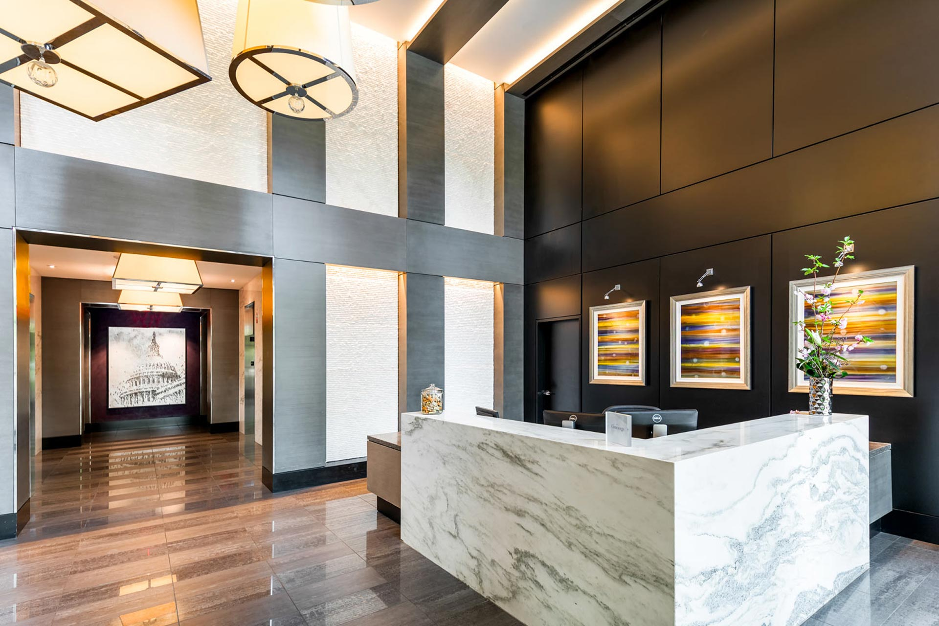 View of modern, marble reception desk with elevator lobby beyond