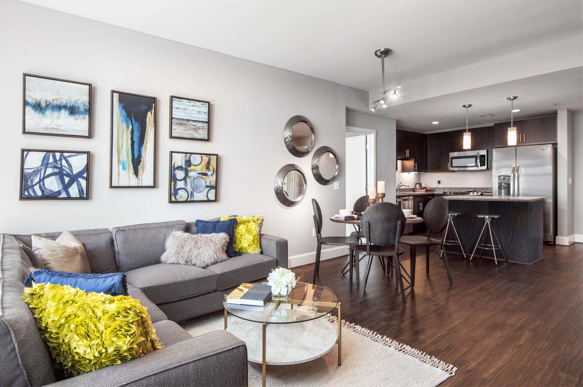Diagonal view of tastefully decorated living room with dining and kitchen spaces beyond