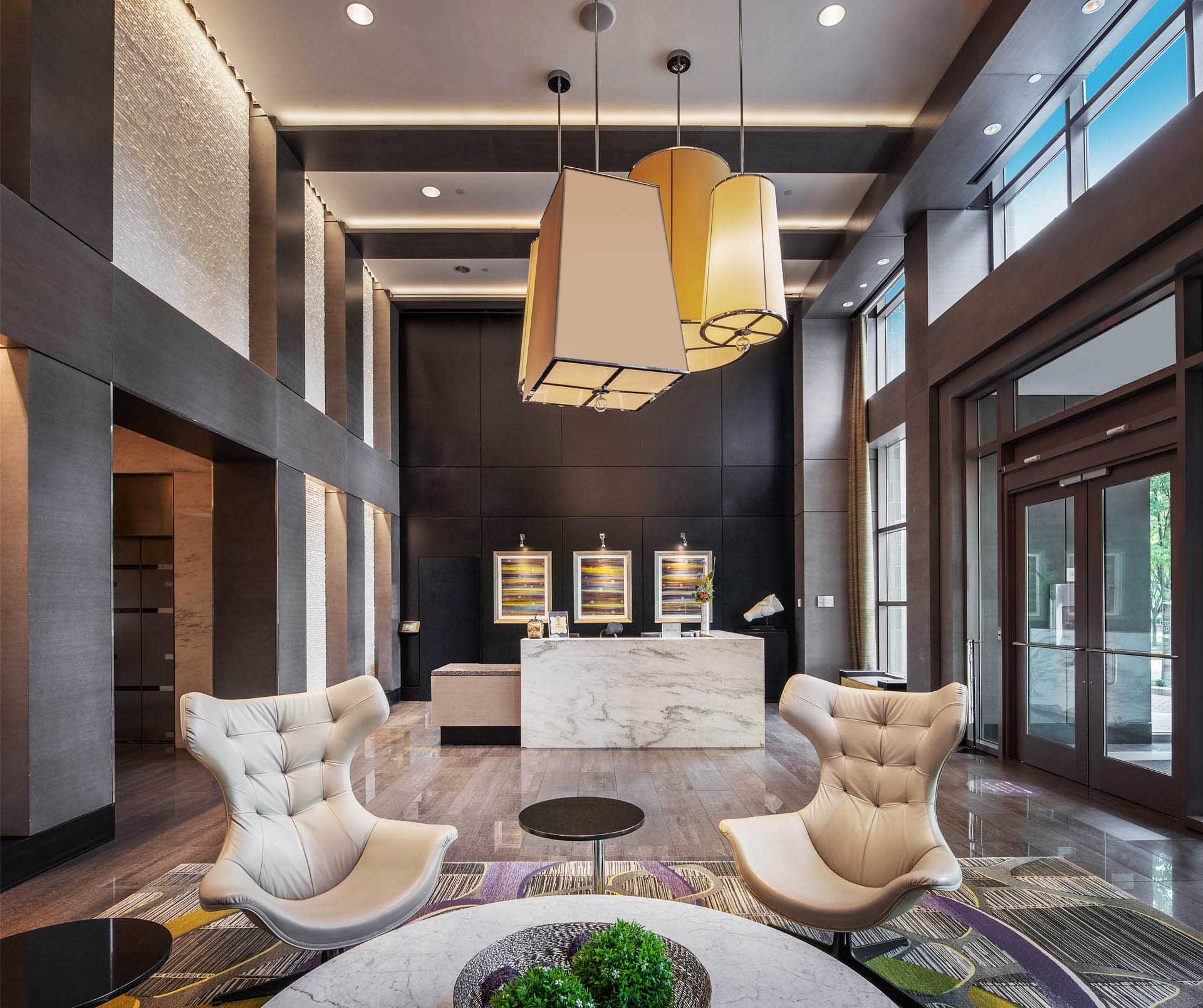 Expansive shot of double-height lobby with white armchairs and marble lobby desk in the background