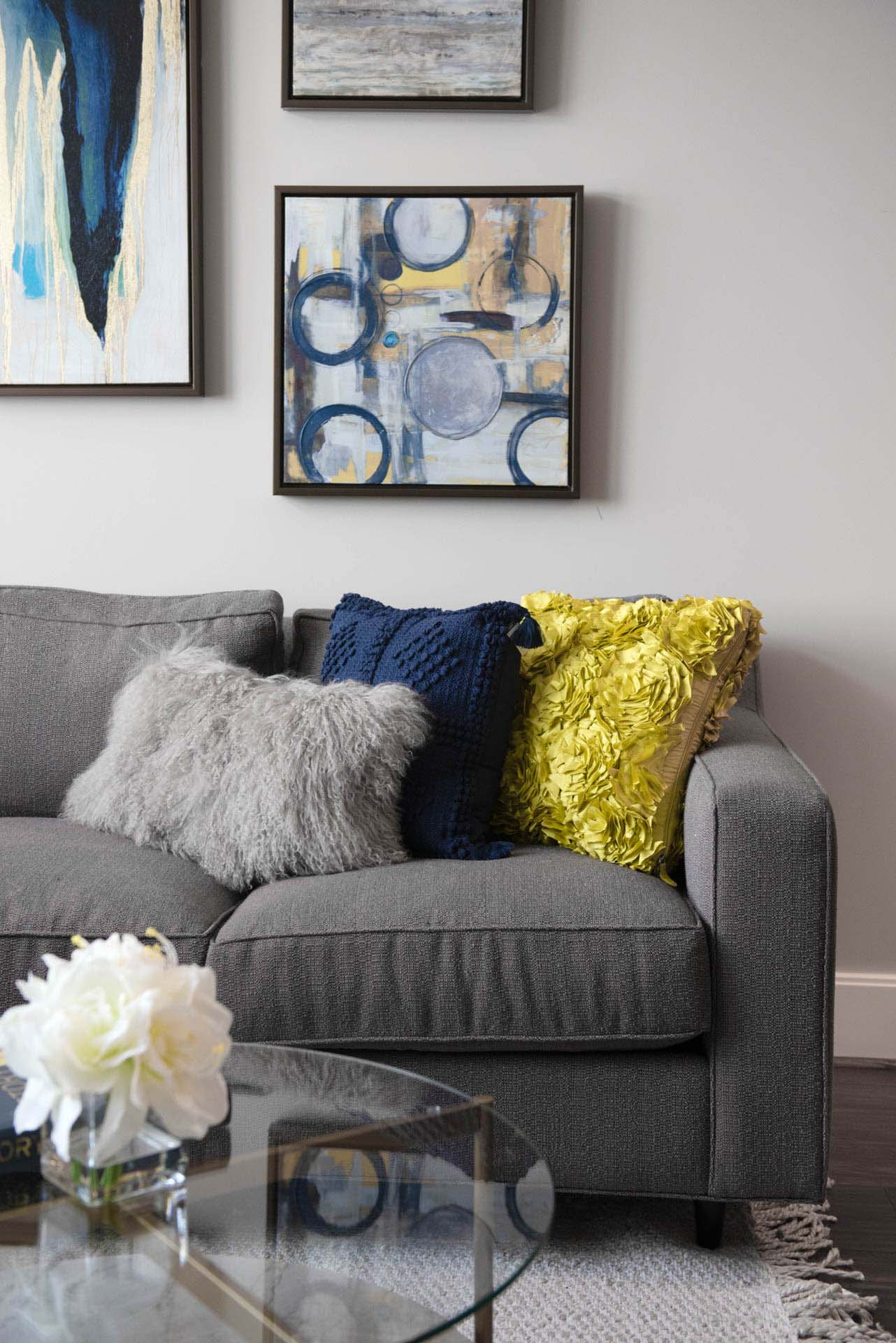 Close in detail of gray couch with blue and chartreuse accent pillows and abstract paintings hanging on wall above