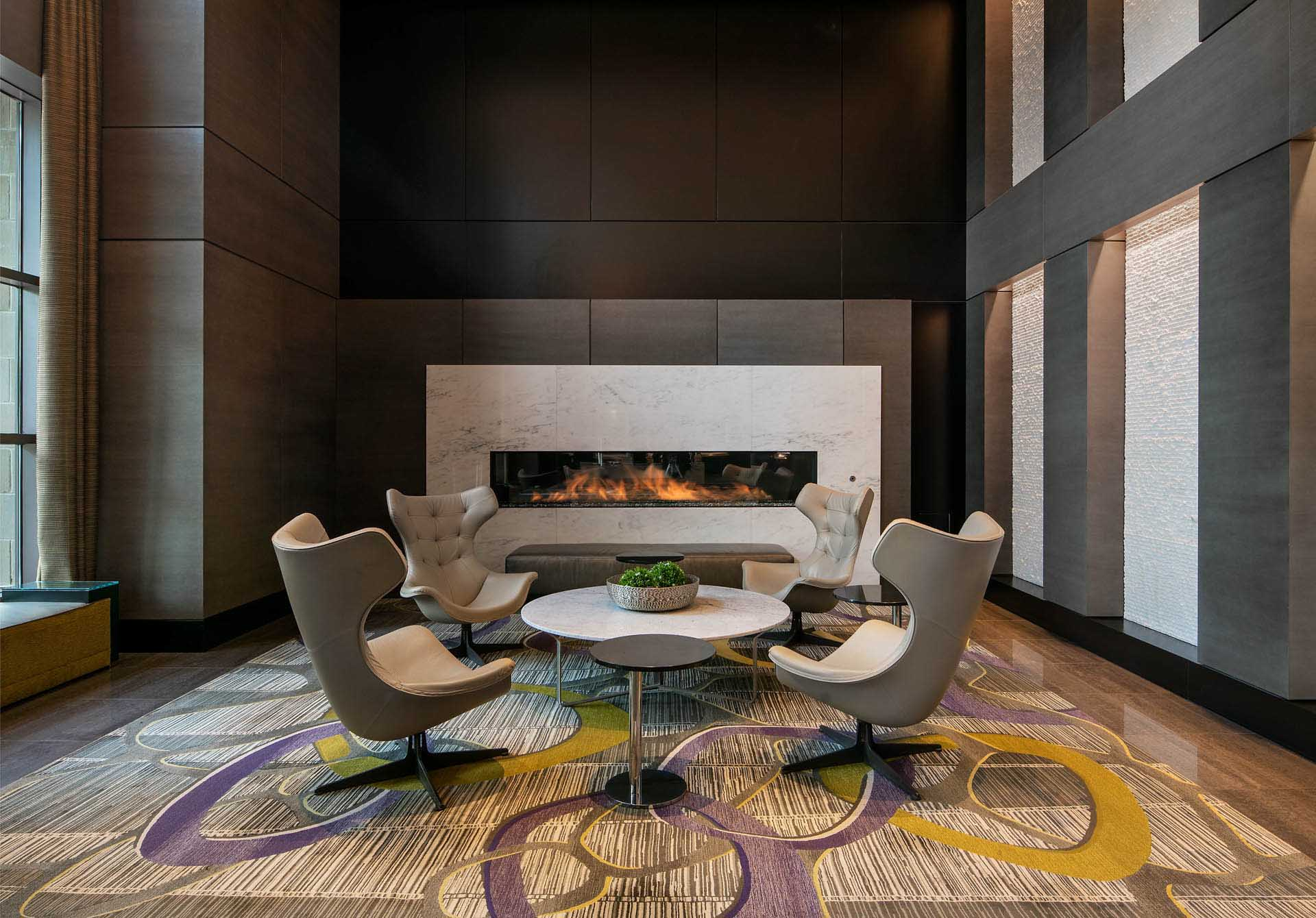 View from reception to lobby seating area with large coffee table and large fireplace