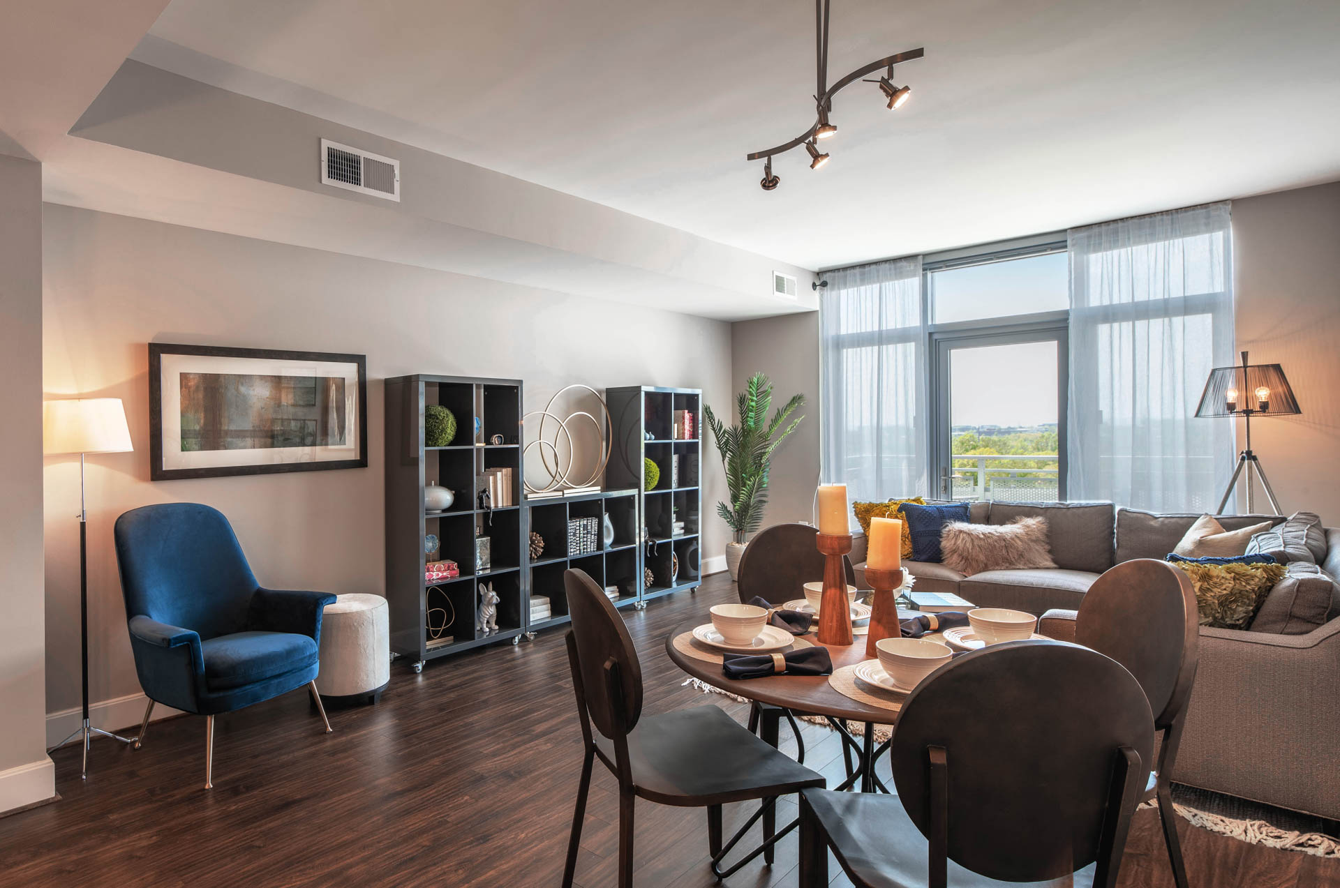 View from dining table to living area with velvet chairs, bookcase, and large windows