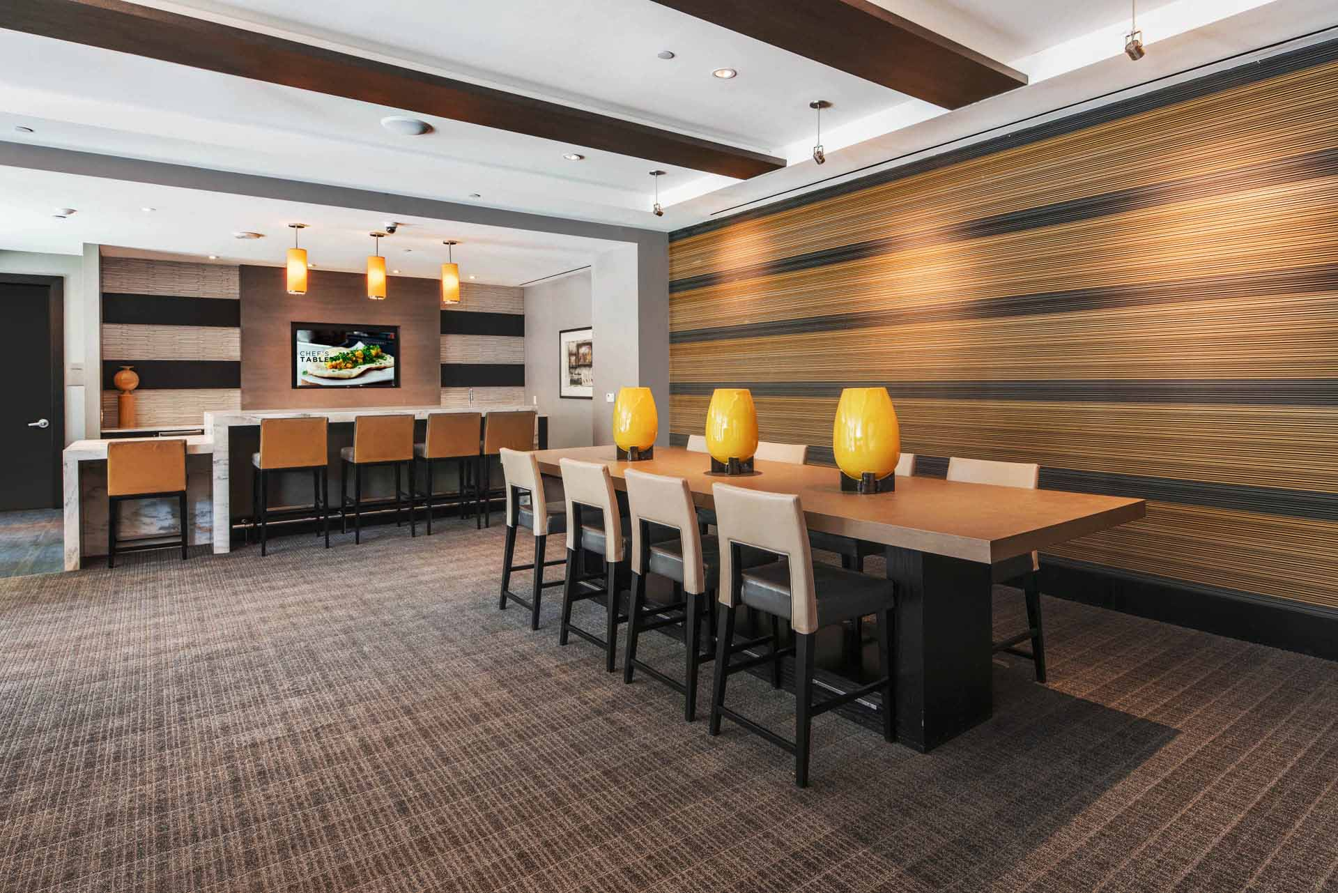 View from resident lounge entertainment area to communal table and bar beyond
