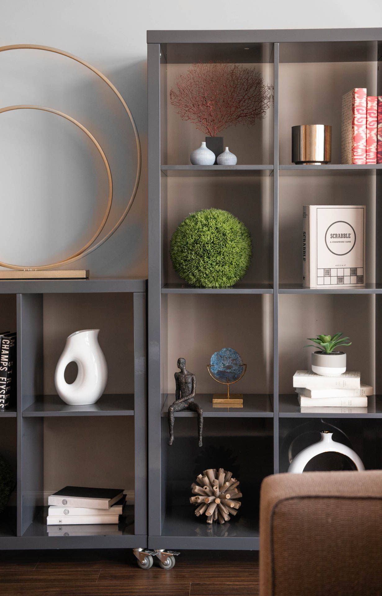 Close in detail of charcoal gray bookcase styled with various books, plants, and art pieces with gold and blue accents