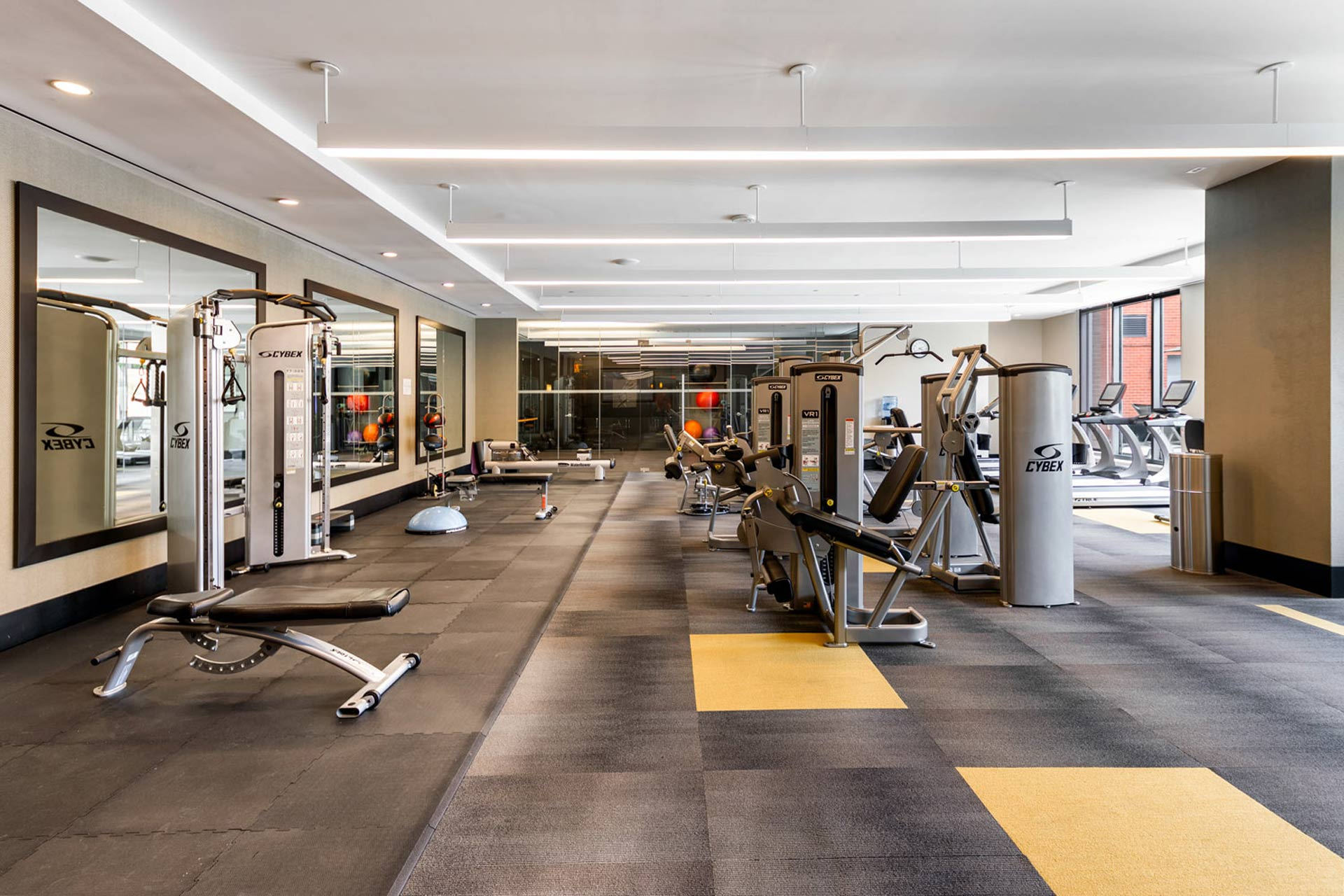 Large, bright fitness center with cardio and strength equipment