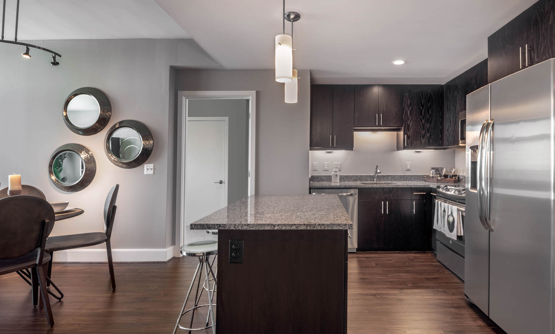 Kitchen with dark wood cabinets, stainless steel appliances, and bar stools at kitchen island