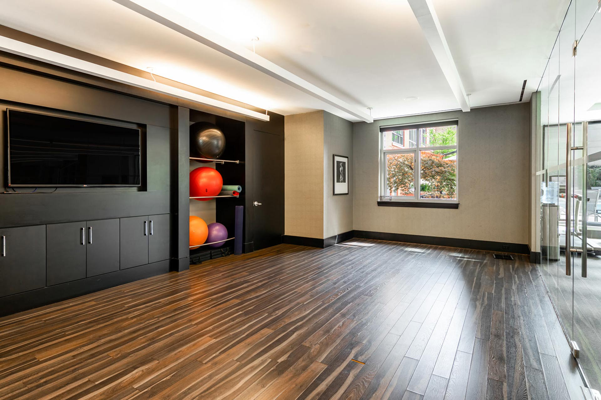 Clean, bright yoga and stretch studio with TV, yoga balls and mats