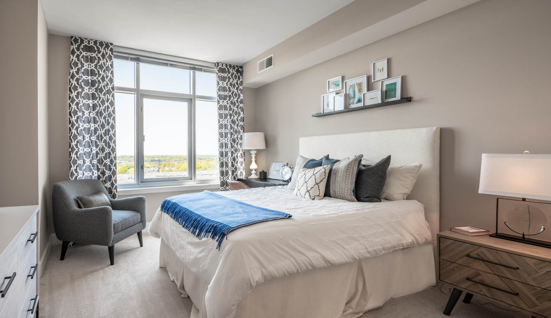 Spacious bedroom with queen bed, tasteful end tables and large window letting in sunlight
