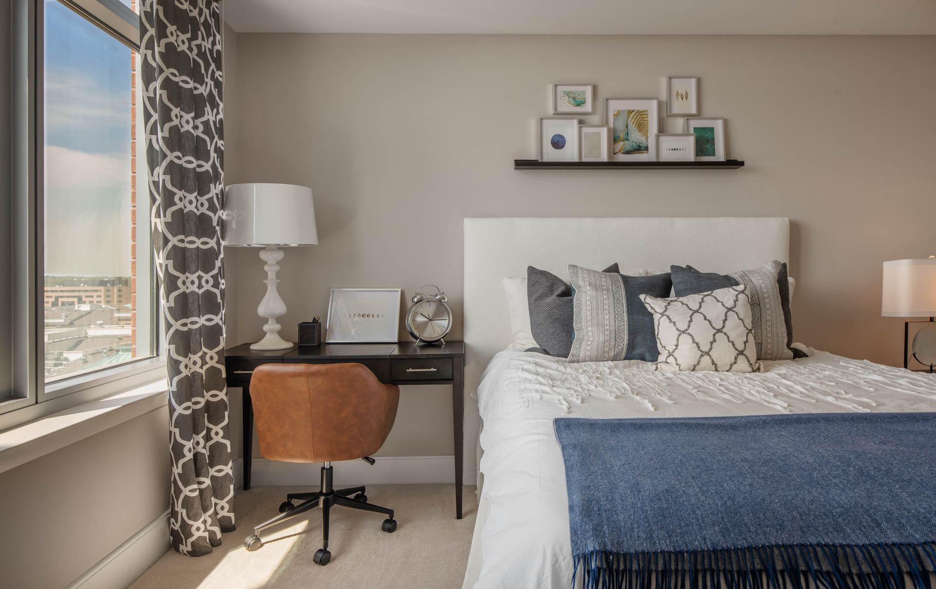 Close in detail of window lighting up queen bed and small desk with bright leather task chair