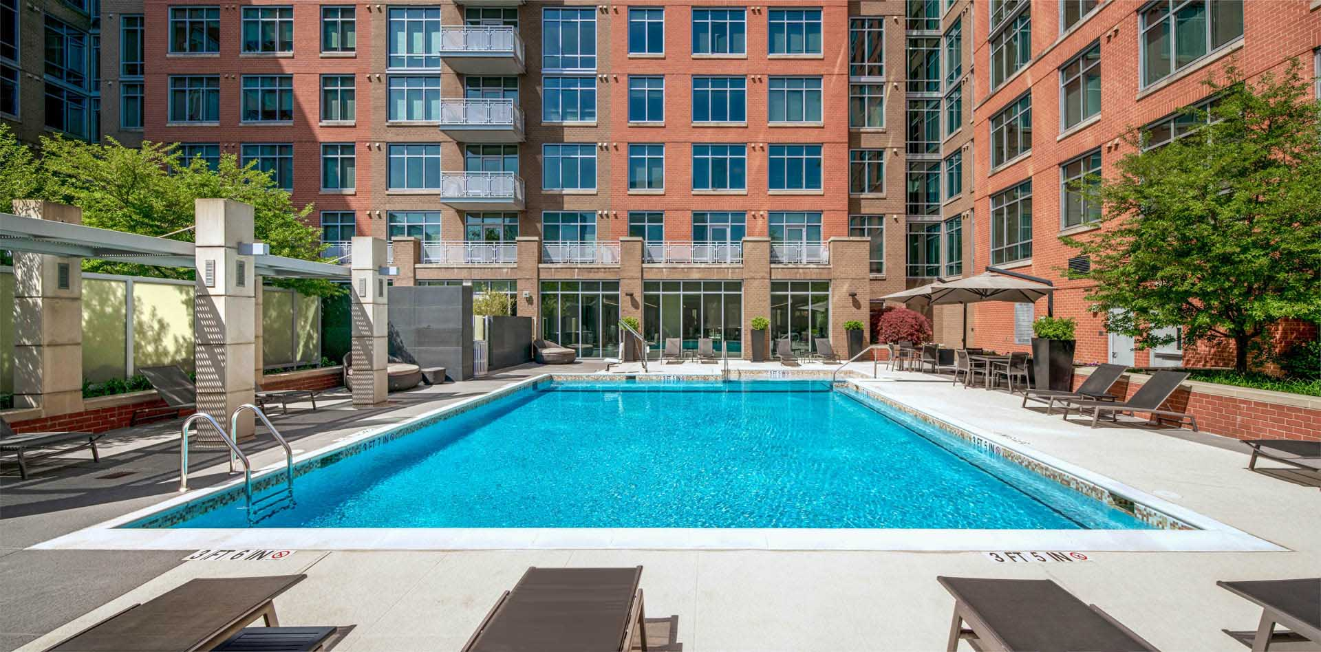 Wide shot of bright pool with lounge chairs and shaded trellis area on the left