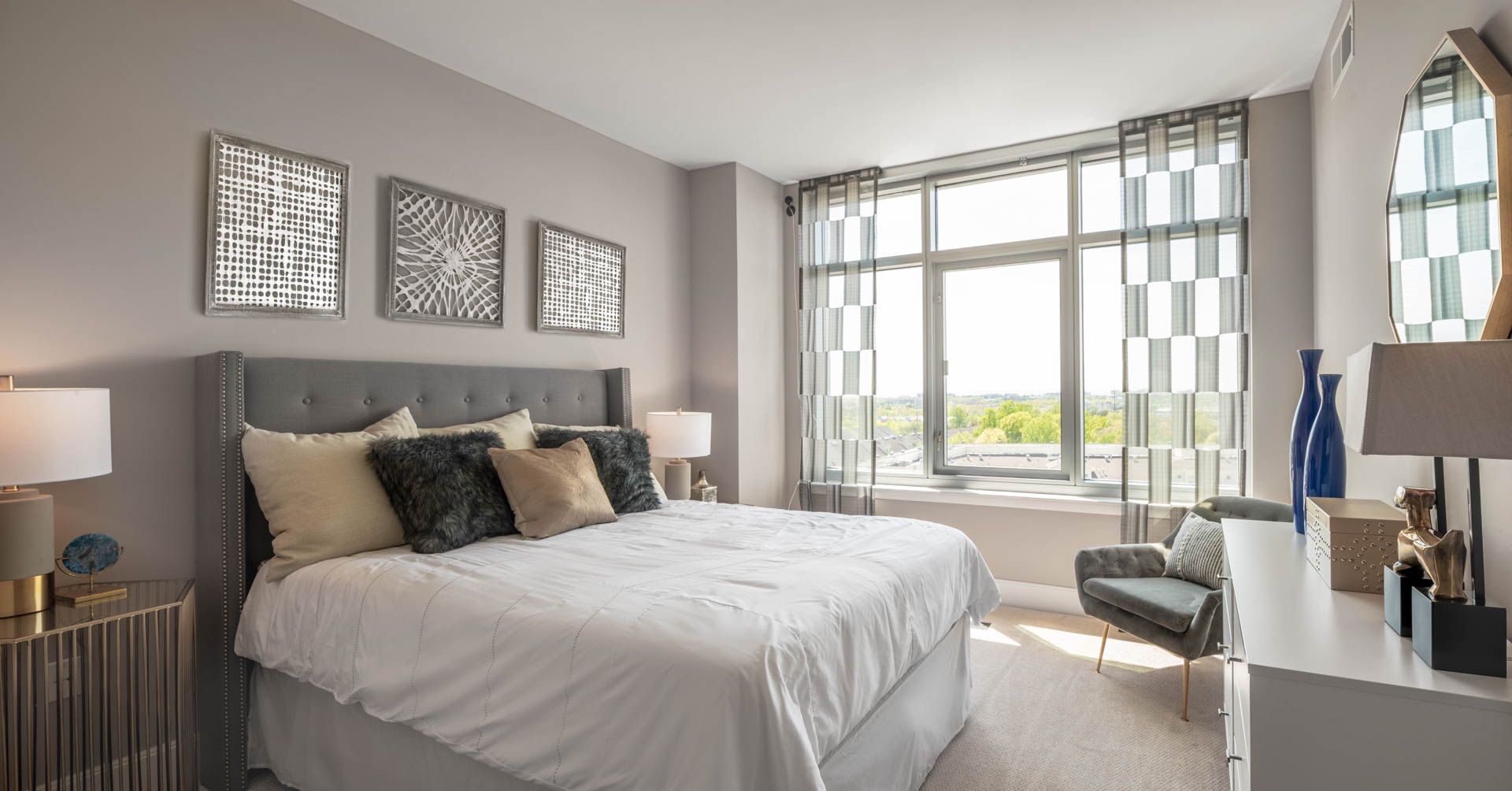 Spacious bedroom with king bed, tasteful dresser and large window with view of treetops