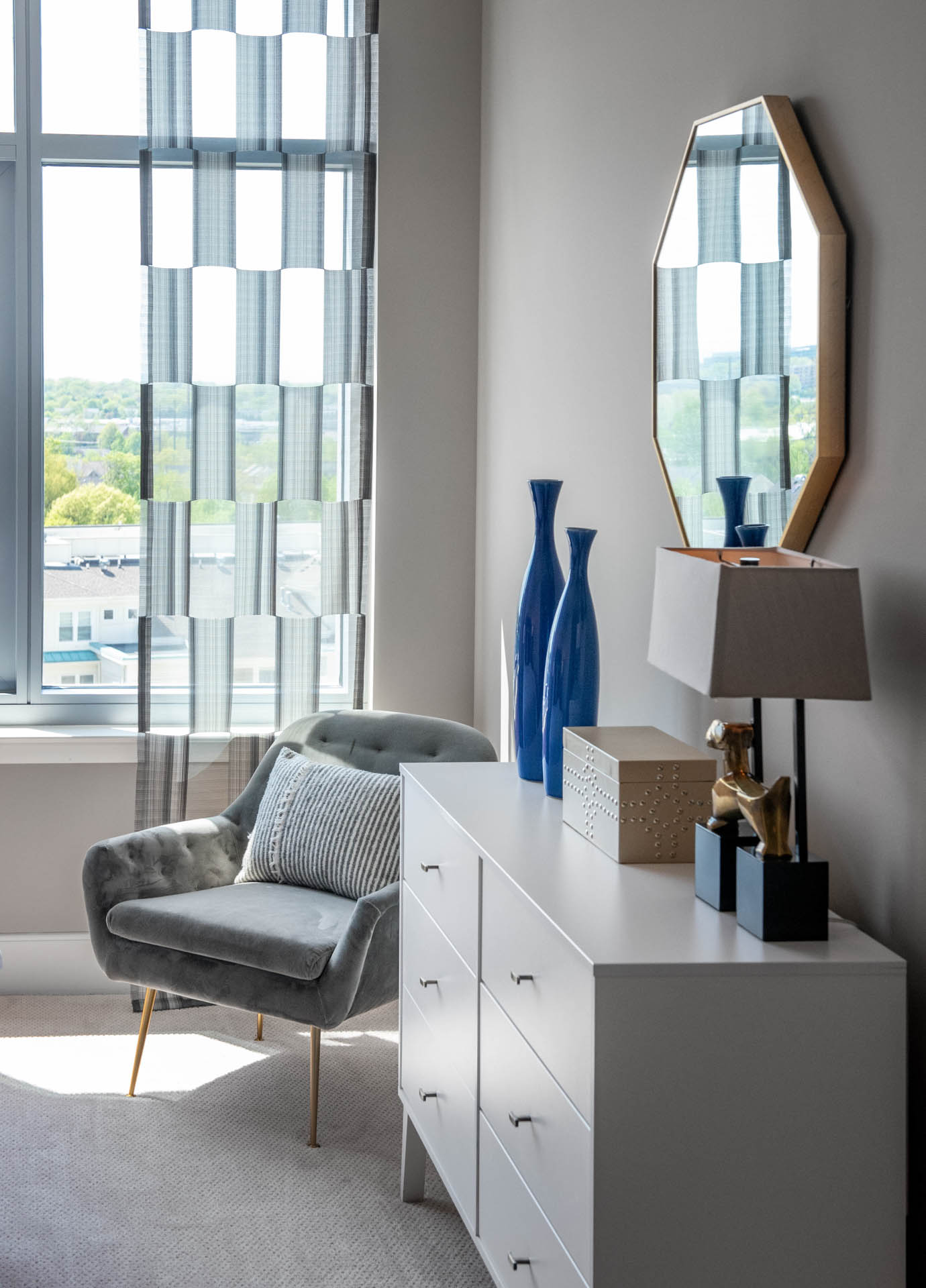 Close in detail of window lighting up gray, midcentury armchair and white dresser