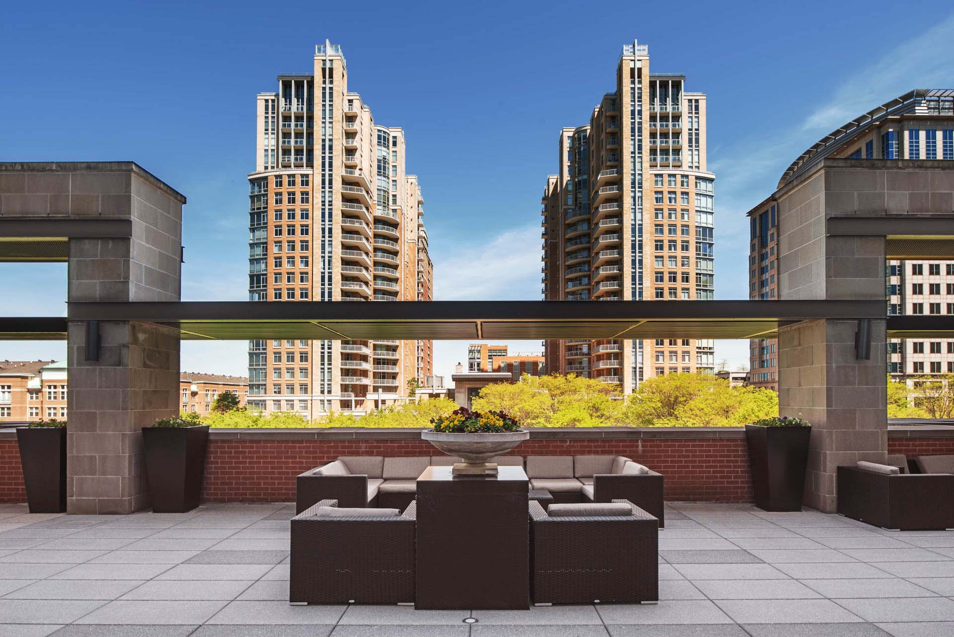 Wide shot of terrace with outdoor seating and towering Reston Town Center buildings beyond