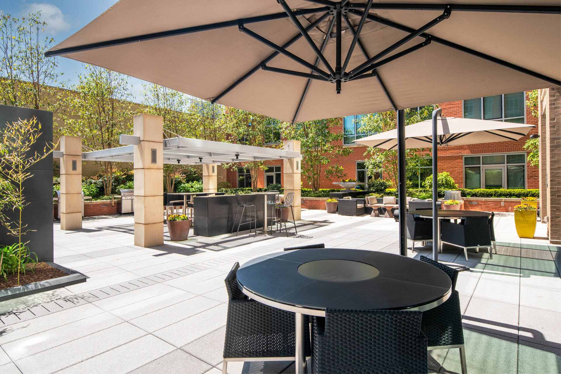 Patio four-top seating under an umbrella, with grills, bar, and lounge seating in background