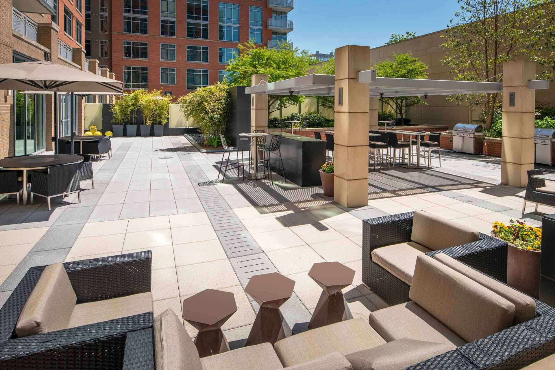 View of large patio with shaded grilling areas, umbrellas, dining space and sofas